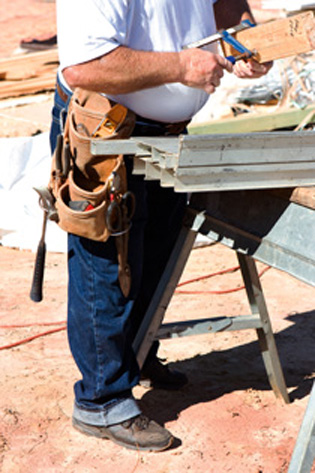 Construction worker with tool belt works with a clamp by a sawhorse.