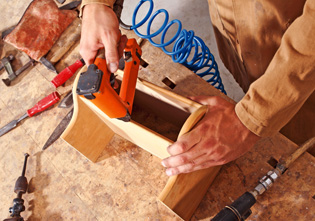 detail of caucasian carpenter at work with tool